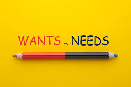 The words wants vs. needs with pencil on yellow background.