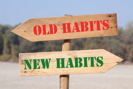 Old Habits versus New Habits text on wooden road sign with left and right arrows.
