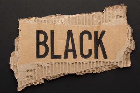 The word black on torn paper on black Фото со стока