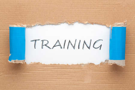 The word training written on white background under torn paper. Business concept