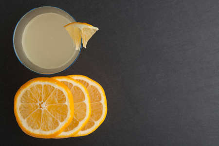 Lemon water in glass with slice lemon on a dark stone background. Top view. 免版税图像
