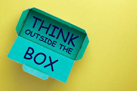 The phrase Think Outside the Box in box on yellow background. 免版税图像