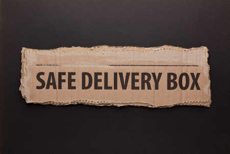 Safe Delivery Box text on torn paper on black background