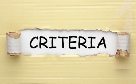 The criteria written on white background under torn paper. Business concept