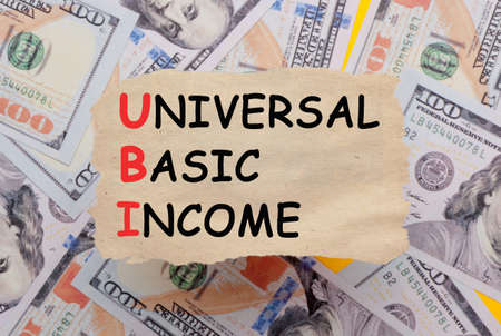 Background of dollar bills with Universal basic income (UBI) text written with marker on old torn paper. Selective focus