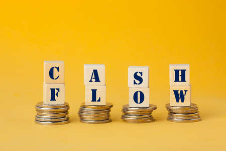 Cash Flow concept with wooden block on step stacked coins on blue background. Business and finance concept. Фото со стока
