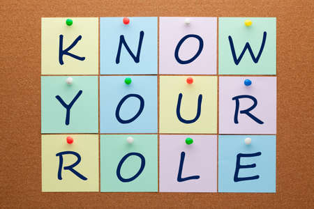 Know your role text on notes pinned on cork board.
