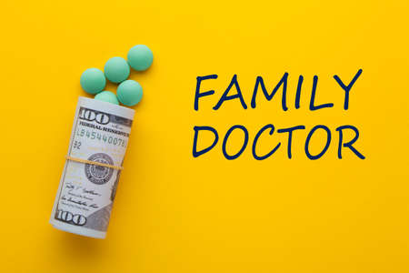 Family Doctor text with medical pills with rolled 100 dollar banknotes on a yellow background. Comprehensive health care