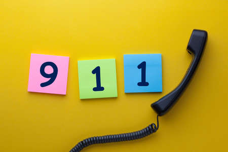 911 (emergency telephone number) written on note with phone handset