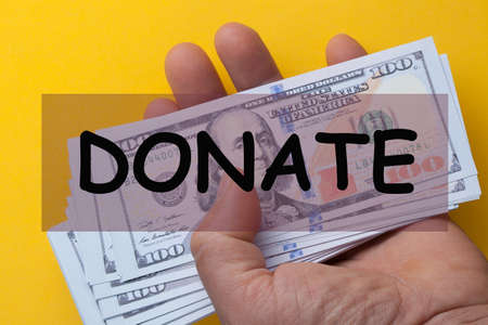 The word donate over hand holding 100 dollar bills on a yellow background. 免版税图像