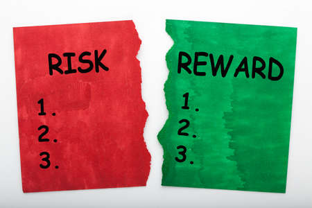 Risk and reward word on green torn paper and red torn paper