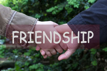 The word friendship over couple holding hands. Motivation inscription