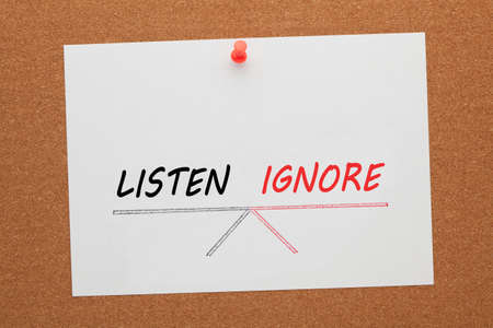 Listen and ignore balance on seesaw drawing on white paper sheet pinned on cork board.