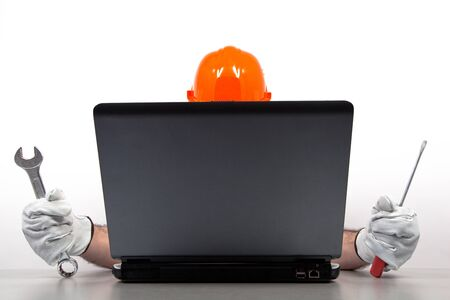 computer help: Mechanic is repairing a laptop, isolated on white  Stock Photo