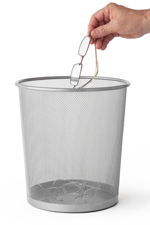 Man throws glasses in the dustbin, isolated on white  photo
