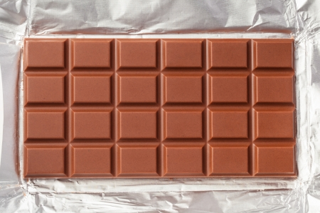 chocolate slice: Milk chocolate bar in opened foil wrapping.