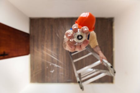 burned out: Electrician on the ladder is changing a burned out bulb.