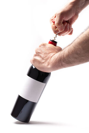 Man is opening a bottle of wine isolated on white background. photo