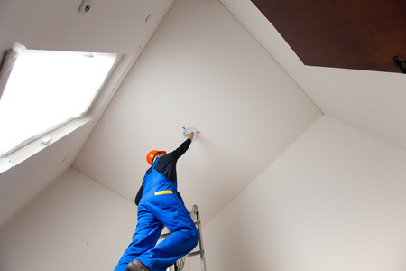 Worker on a ladder prepares a room for painting photo