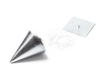 plummet: Metal plummet in the form of a cone white cord and plank. The objects are laid on the table and isolated on white. Stock Photo