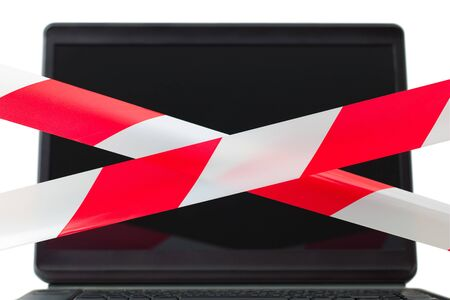 limitation: Two red and white barrier tapes are crossed in front of a computer display. The composition symbolized limitation of use of the computer Internet chat. Also warning about dangerous content and influence. Stock Photo