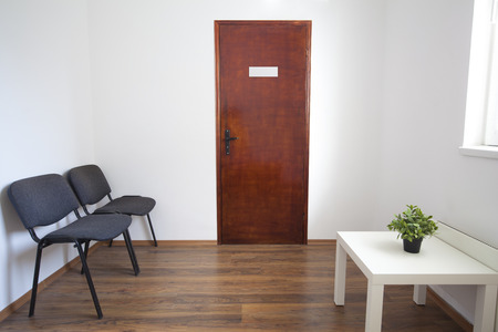 Small white waiting room without people. A doctor, dentist or other medical practitioner provides this room for the use of people who are waiting to be seen. The wooden door is closed and furniture is two chairs, small table with green plant. Stock Photo