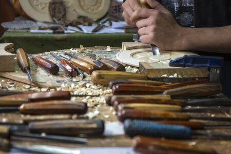 trinchante: Artesano, tallador de madera está trabajando en los detalles de una placa de madera. Él está en el taller y en la mesa de trabajo se puede ver una gran cantidad de herramientas y scobs madera.