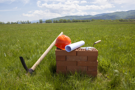plummet: Bricks, trowel, blueprint on a roll, plummet, pick axe and hardhat prepared for beginning of construction of a new building. The tools are put on a green wide meadow. The pick axe is stuck in the ground.