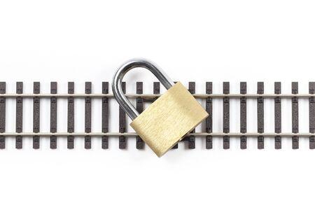 railway tracks: Metal railway tracks with locked padlock on them, isolated on white background. Stock Photo