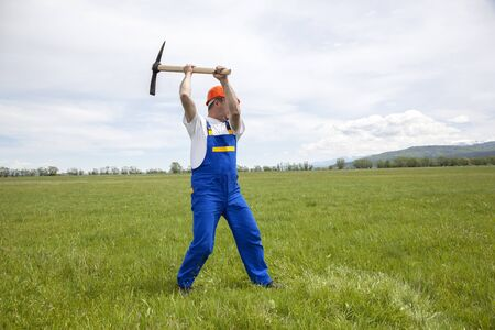 pickaxe: Worker with pickaxe is digging on a wide green field.
