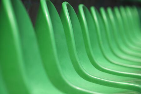green been: Empty green plastic stadium seats arranged in a row. The image has been made before the beginning of a tennis game. Stock Photo