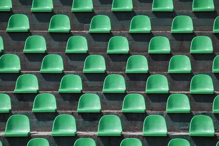stadium: Image of green plastic stadium seats in rows. The seats are filled the frame as background. This is a day shot of an empty stadium.