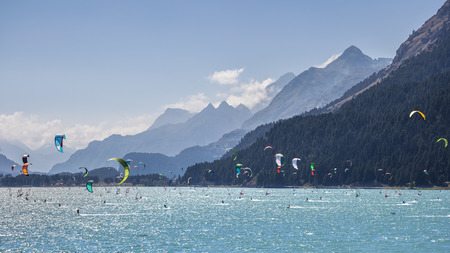 windsurfers: Mountain landscape with a lot of kite surfers and  windsurfers moving in a lake. They use the wind to move their boards on the water. Mountains are as background in a sunny day.