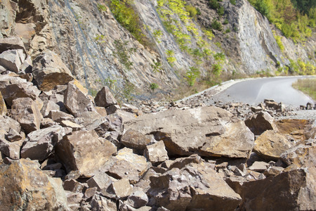 landslip: Image of a closed road by a pile of fallen big and small stones. This dangerous accident is caused by a landslide. Stock Photo
