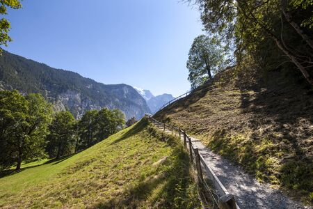 meandering: Landscape with a small mountain path and handrail around it. The meandering pathway leads up the mountain. It is a sunny summer day and the glacier can be seen in the center. Stock Photo