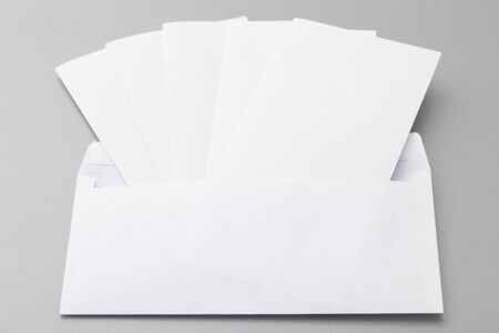 spread sheet: Five folded white sheets put in blank white envelope, isolated on background.