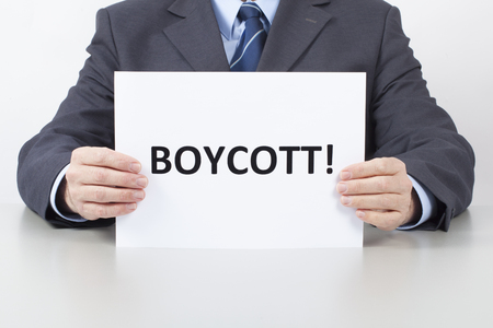 Man in suit sitting behind an office table and holds a white sheet with text Boycott in his hands.