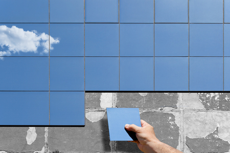 Conceptual image of renovation and insulation of the wall of an old building. A human hand puts and mounts new modern glass plates on the facade.