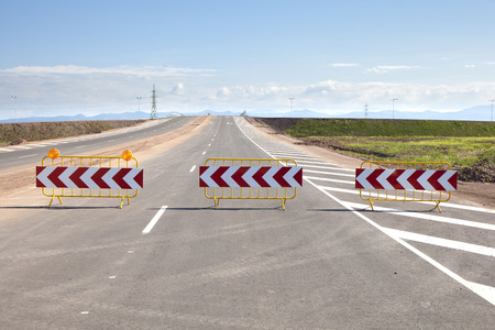 Three road signs barriers bordering a new road under construction. Banco de Imagens