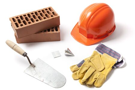 plummet: Several construction accessories trowel, bricks, plummet, hard hat and gloves isolated on white background.