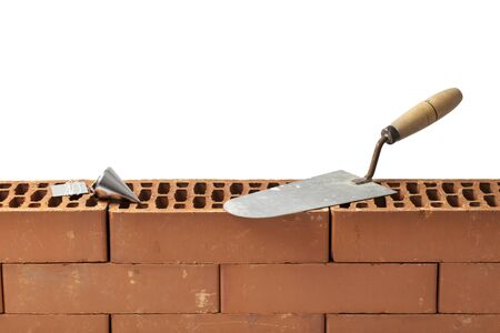 plumb: Construction tools trowel and plumb bob left on a new brickwork isolated on white. Stock Photo