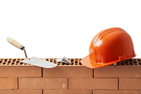 plumb: Construction tools trowel hard hat and plumb bob left on a new masonry isolated on white.