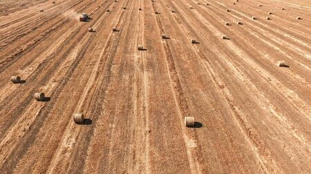 baler: Aerial image of a tractor straw baler working in an agricultural field.