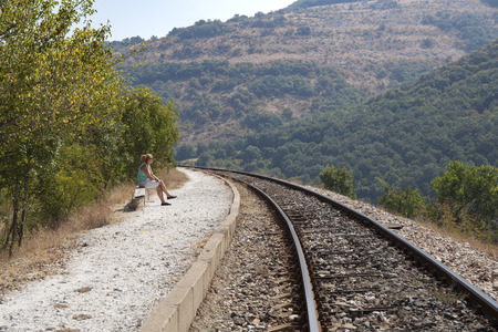 baggage train: Woman without baggage waiting for a train at a small rural train station in a sunny summer day.