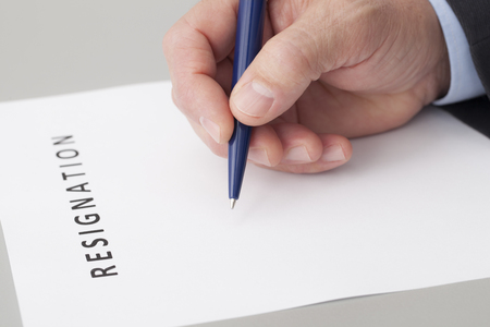 resignation: Man with a pen in the hand, writing a letter of resignation on a table Stock Photo