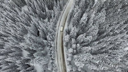 Snowy and frozen winter road with a moving car on it. Stock Photo