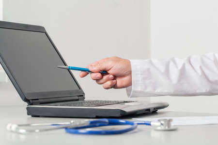 commenting: Doctor practitioner pointing showing by the hand to the computer screen in the consulting room.