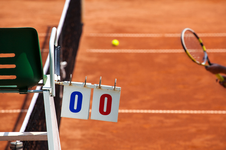 Tennis player umpire chair with scoreboard and racket on a clay court in the beginning of the game.