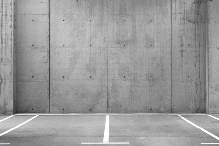 Meerdere lege parkeerplaatsen in een open garage met betonnen muur