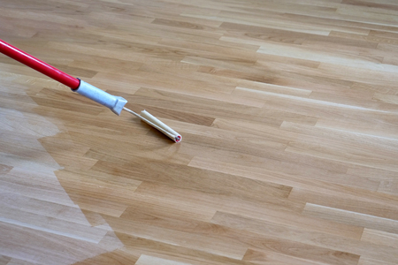 Varnishing lacquering an oak parquet floor by paint roller first layer.